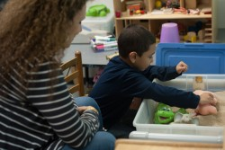 Erie Neighborhood House psychologist Elizabeth Yelen works at a sandbox with 5-year-old Anjel. The sandbox is used in play therapy sessions with young children to help them express thoughts and feelings. (Photo: Julienne Schaer)