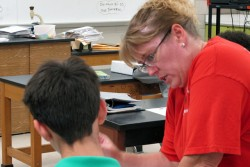 Monroe Middle School science teacher Andrea Groves works with a student on a project. Common Core State Standards encourage more reading and writing in classes like science, social studies and physical education.