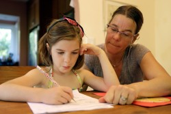 """Stacey Jacobson-Francis works on math homework with her 6 year old daughter Luci Wednesday, May 14, 2014, at their home in Berkeley, Calif. As schools around the U.S. implement national Common Core learning standards, parents trying to help their kids with math homework say that adding, subtracting, multiplying and dividing has become as complicated as calculus. Stacey Jacobson-Francis, 41, of Berkeley, California, said her daughter's homework requires her to know four different ways to add. """"That is way too much to ask of a first grader. She can't remember them all, and I don't know them all, so we just do the best that we can,"""" she said. (AP Photo)"""