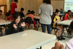 A fifth-grader reacts with excitement to her early lead in math specialist Josh Rosen's annual KenKen challenge. (Photo: Pat Wingert)