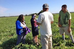 Family service workers Yeny Gutierrez and Daniela Hernandez talk to local farm workers about the area's Migrant Head Start centers. (Photo: Kyle Spencer)