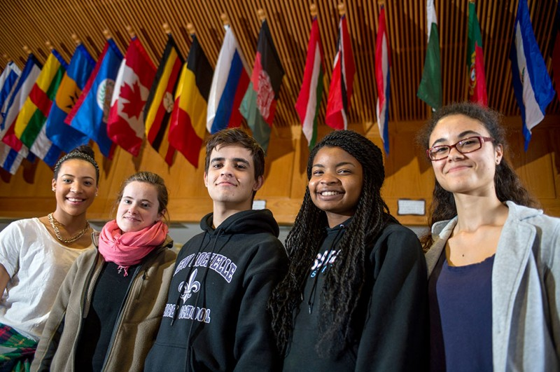 From left, New Rochelle High School seniors, Matisse Clayton, Haleigh Doherty, Esteban Acevedo, Adaugo Ezike, and Camille N'Diaye-Muller stand in front of international flags posted in the main entrance of New Rochelle High School on January 23, 2014 in New Rochelle, New York. Photo by Ann Hermes/The Christian Science Monitor
