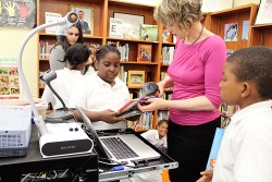 School librarian Shannon Englebrecht reminds Tori Reese, 8, that she has several books overdue. Englebrecht allows students at Charles Drew Preparatory Academy, a public school in San Francisco, to check out as many books as they want. Credit: Lillian Mongeau, EdSource