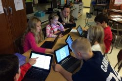 Students make use of tablets and technology while working in small groups.