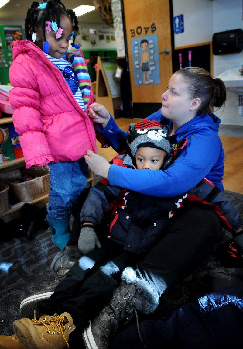 Pre-kindergarten teacher Jaime Linton zips up the jacket of Aniya Harrell, left, as Demariay Gunn sits in her lap before recess in a pre-kindergarten class at New Horizon Academy in St. Paul. (Jean Pieri / Pioneer Press) No reproduction