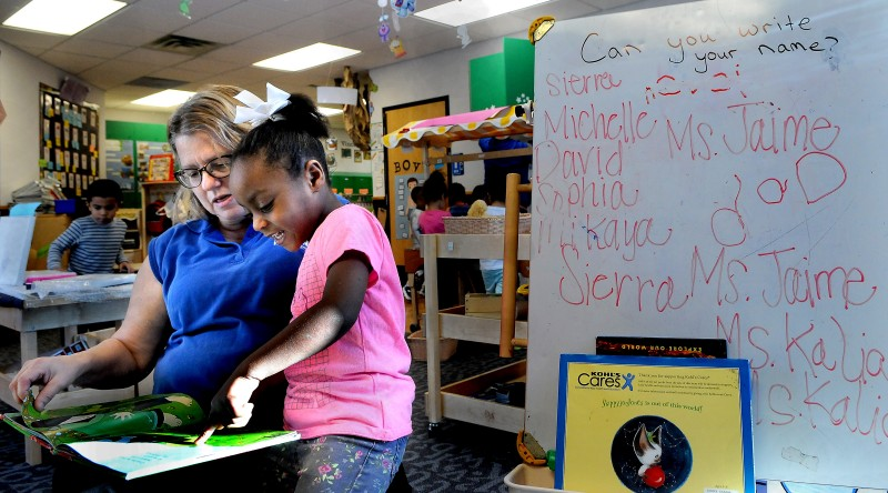Pre-kindergarten teacher Robin Dike reads Red Is a Dragon with Michelle Adams at New Horizon Academy. (Jean Pieri / Pioneer Press) No reproduction