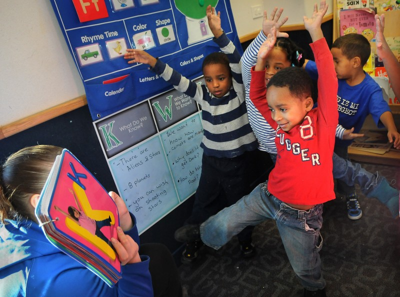 """Children try to form the letter """"K"""" in a yoga alphabet book held by their pre-kindergarten teacher Jaime Linton at New Horizon Academy. (Jean Pieri / Pioneer Press) No reproduction"""