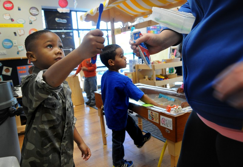 After he brushes his teeth, Demariay Gunn hands his toothbrush back to his teacher at New Horizon Academy. (Jean Pieri / Pioneer Press) No reproduction