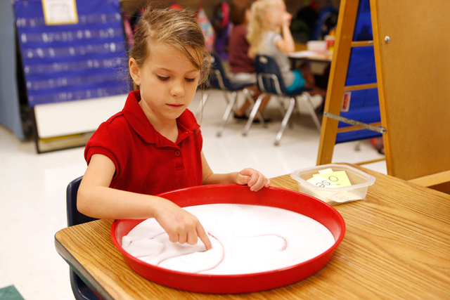 Kindergartner Beth Capperman writes sight words in a tray of salt during a literacy lesson in Candace Cherry's classroom at Saltillo Primary. (Photo: Lauren Wood/Northeast Mississippi Daily Journal)