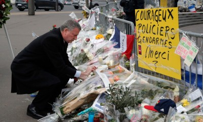"""New York city mayor Bill de Blasio lays a wreath of flowers at the kosher grocery where Amedy Coulibaly killed four people in a terror attack, in Paris, Tuesday Jan. 20, 2015. Brothers, Said and Cherif Kouachi and their friend, Amedy Coulibaly, killed 17 people at the satirical newspaper Charlie Hebdo, a kosher grocery and elsewhere last week. The yellow poster reads: """"Brave police officers and gendarmes, Thank you."""""""