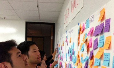 High School design team members check out ideas written on post-it notes during a brainstorming session.