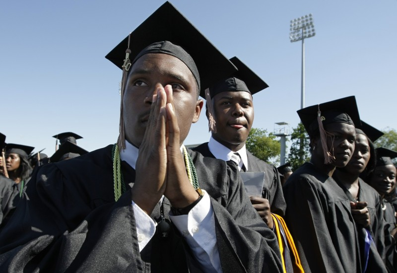 Ryan Brown of Deptford, NJ, and other seniors wait in anticipation for President Barack Obama to addresses the 1,200 graduates of Hampton University, a historically black university, at the school's Armstrong Stadium, in Hampton, Va., Sunday, May 9, 2010.