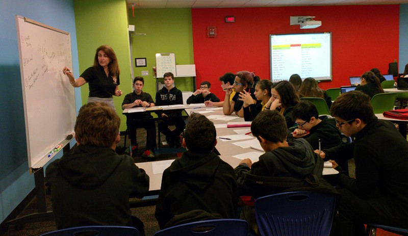 Teacher Grisel Mesa works with a small group of students in a blended learning classroom at W.R. Thomas Middle School.