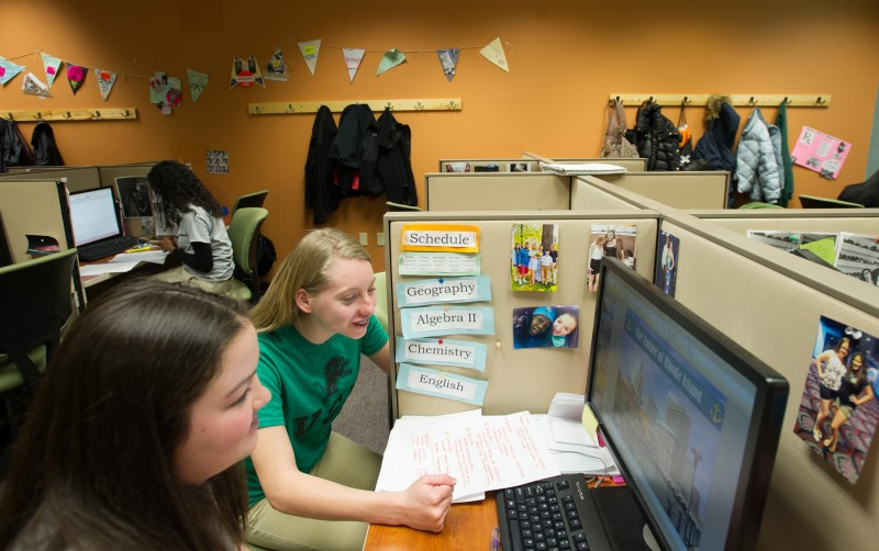 Village Green Virtual students Taylor Malone, 16, of West Warwick, second from left, and Caroline Boyle, 16, of Cumberland review Boyle's powerpoint presentation inside their Learning Center. Instead of traditional classrooms, Village Green students have learning centers in which they have individual computer work stations.
