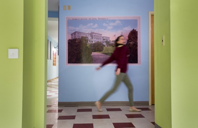 Village Green Virtual junior Dylhan Waterman, 17, walks past a mural that depicts an old image of Providence, Rhode Island.