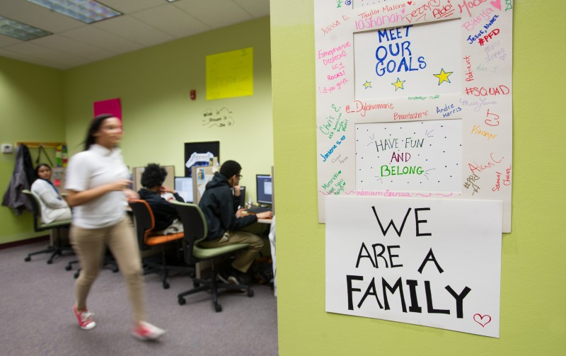 A hand made sign with the signatures of members of the Village Green Virtual junior class hangs in a learning center.