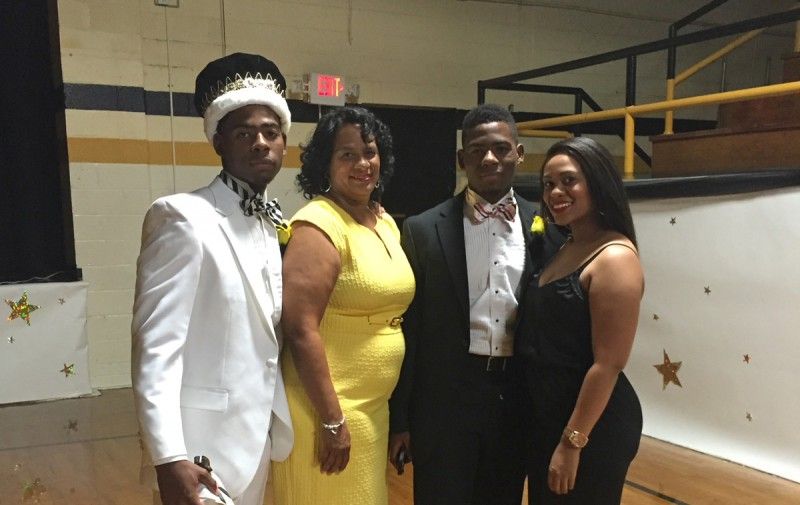 "Muave Sanders with his mother, Lenden; twin brother Suave; and sister, Jasmine, in the gymnasium of East Side High School after Muave was crowned ""Mr. East Side High 2014."""