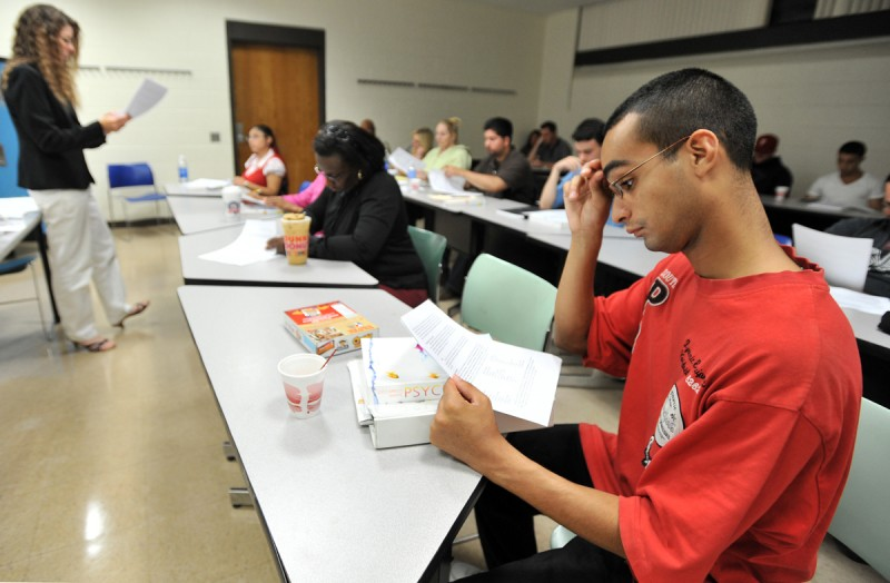 In this Sept. 8, 2009 file photo, Hector Gonzalez, 23, of Chelsea, Mass., right, looks over the course syllabus distributed by professor Kathleen O'Neill, left, for a psychology course at Bunker Hill Community College in Boston.