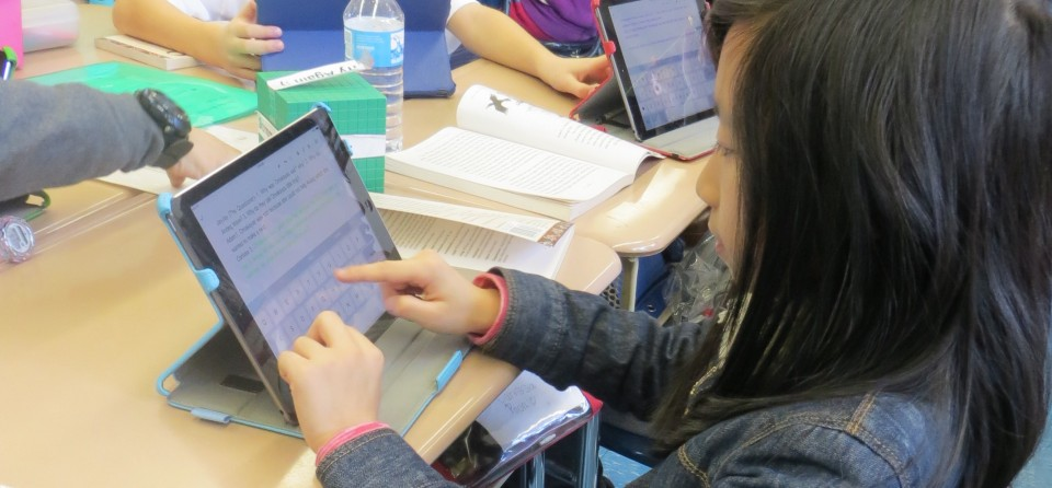 Carissa, a fourth-grader at P.S. 101, uses Google Docs on her classroom iPad to discuss themes in the class's latest book with her group.