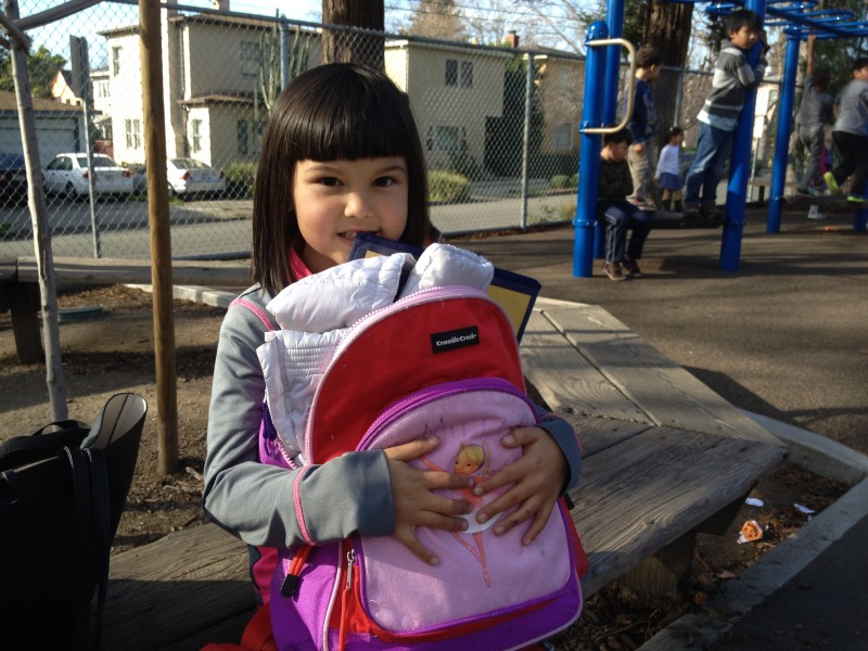 Miriam Foster, 6, a kindergartener at Emerson Elementary School (with her mom, with Mom Tawankon, 31) in Berkeley, California, where schools have stopped using textbooks, making backpacks lighter.