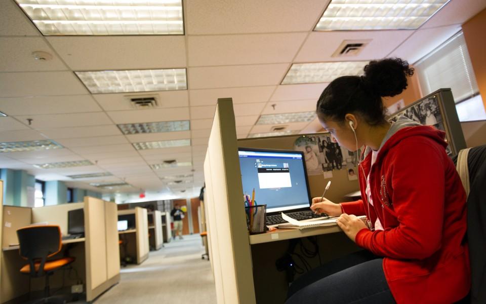 Village Green Virtual sophomore Francheska Rodriguez, 17, of Providence writes at her work station in her blended learning center.