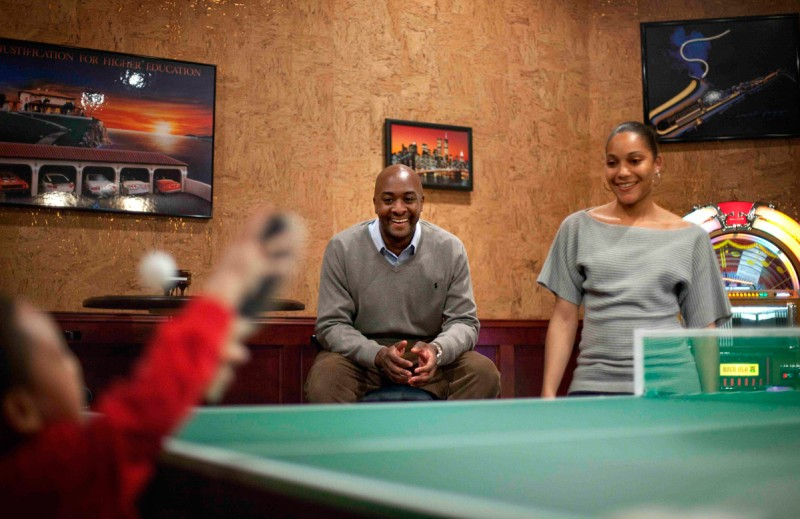 Shelton Haynes, 33, center, looks on with wife Tiisha, right, as son Jamir, 2, plays ping pong on a visit to Haynes' parents home Tuesday, Feb. 15, 2011 in Duluth, Ga.