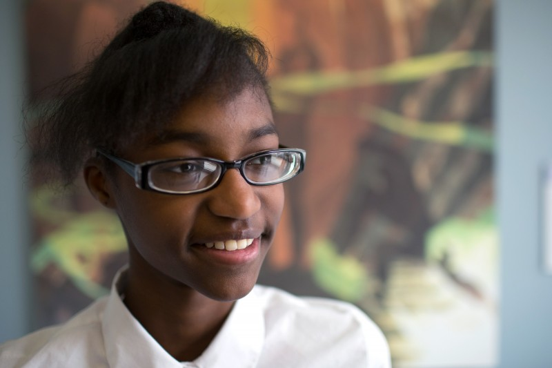 """Zarria Porter, 14, stands in front of """"Song of the Towers,"""" her favorite of the 69 paintings replicated to hang in her school."""