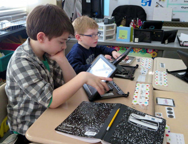 As Joshua Parr (left) and Timothy Gorman work on a math problem on iPads, their old-fashioned notebook lies within reach. Their teacher, Morgan Mercaldi, says she strives to balance the amount of time her students spend on and off their electronic devices.