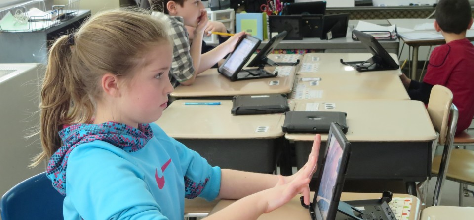 Keira McCaffrey uses her iPad to figure out the area of a rectangle. During the math lesson, she and the other third-graders will use their tablets for some problems, paper and pencil for others.