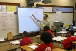 David Woodside, a seventh-grade math teacher at Taft Junior High in Oklahoma City, reviews a problem on the smart board.