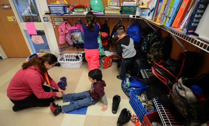 Anitrea Provencher, who is interning at the Pittsfield Elementary School, helps kindergartner Logan Leduc change from his snow boots to sneakers.