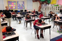 In this April 14, 2015 photograph, third grade students in Stephanie Slayter's class at Cherokee Elementary School in Pascagoula, Miss., wait for teachers to pick up computers after completing a computerized 50-question multiple choice third-grade reading test. Across Mississippi, 38,000 third graders, their parents and teachers are waiting to find out whether they'll be moving on to fourth grade.