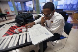In this Friday, Feb. 8, 2013 photo, Xavier University student Triton Brown studies in a common area on campus before going to one of his part time jobs in New Orleans. Thousands of students unexpectedly either had to stay at home, transfer to a less expensive school or find new money when the U.S. Department of Education quietly changed how it evaluated the credit of parents applying for a federal PLUS loan. Brown, a Milwaukee native who is a freshman at Xavier University of Louisiana, said his family was counting on a PLUS loan, but his mother's application was rejected after he had been accepted the previous semester.