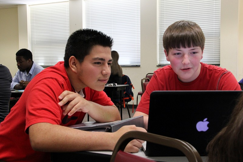 Sixteen-year-old Julio Martinez and 15-year-old Aaron Penny read and joke together during a free period at Johnston County Early College Academy on April 24.