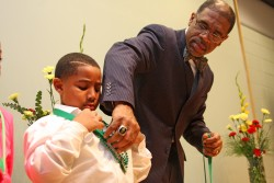 McComb Superintendent Cederick Ellis untangles a student's medal from his beaded necklace. Ellis honored students who maintained an A average for three consecutive grading periods.