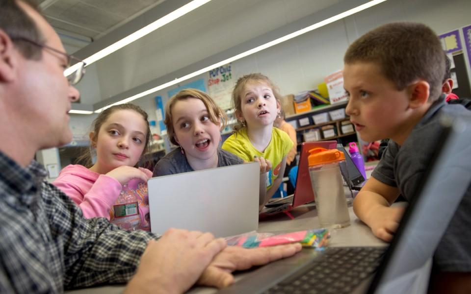 Greenbush elementary school fourth-grade teacher Chris Allen, left, works with, from left, Alexa Stroker, Elissa Dorgan and Connor Moreau on a math problem.
