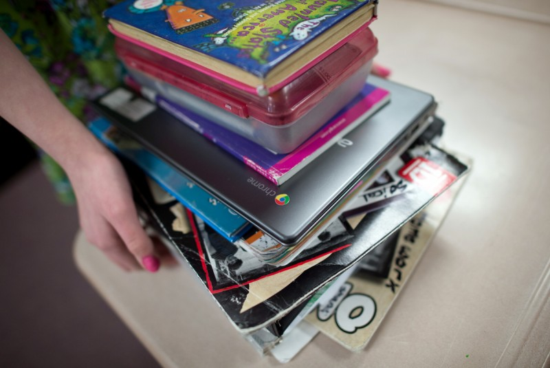 A Deering Middle School student gathers her binders and Chromebook as she waits to go to her next class.