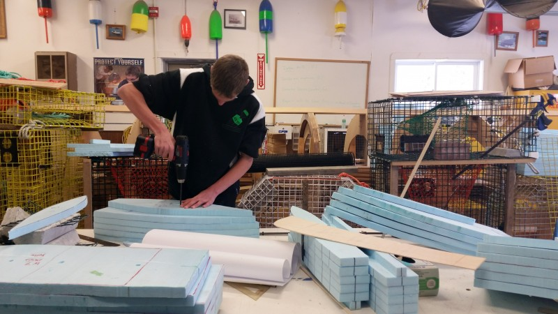 A Deer Isle-Stonington High School student works on a Styrofoam model of a boat hull he created in a math and science class. The school has created a new curriculum to show students the relevance of their classes to prospective future careers in the fishing industry.