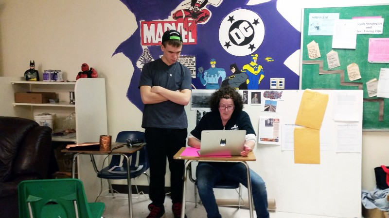 Deer Isle-Stonington art teacher Katy Helman works with a student in a class combining U.S. history with the arts on a project about Prohibition.