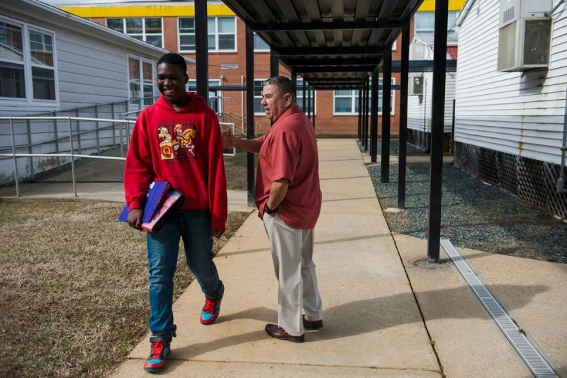 Jalen Williams, 14, left, walks past Jose Diaz, MCJROTC Instructor, on his way to Marine Corps Junior ROTC class at Quantico Middle/High School on March 13, 2015 in Quantico, VA. The Department of Defense Education Activity (DoDEA) campuses are typically smaller than traditional public schools,with a more experienced teaching staff.