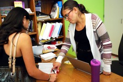 College Advising Corps adviser Carmen Macias, right, explains yet another form to a Torres High School students in East Los Angeles.
