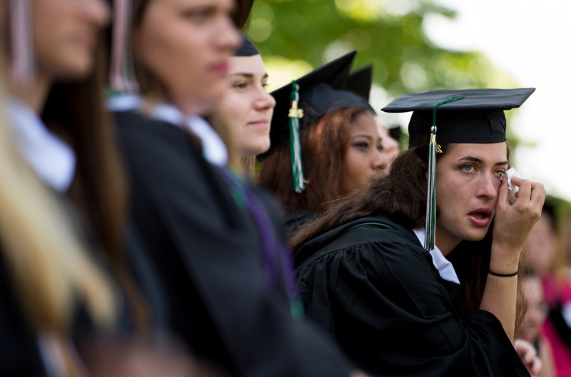 A Sweet Briar College graduate wipes away a tear during commencement exercises Saturday morning, May 16, 2015 near Amherst, Va. The school announced plans to close earlier in the year, potentially making the class of 2015 the school's last.