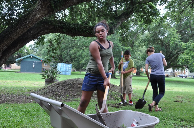 Saniyah Barthelemy, 11, digs a trench as her class works on building a rain garden to fix a drainage problem at Arthur Ashe Charter School. Barthelemey will enter sixth grade this fall at Langston Hughes Academy, another FirstLine school.