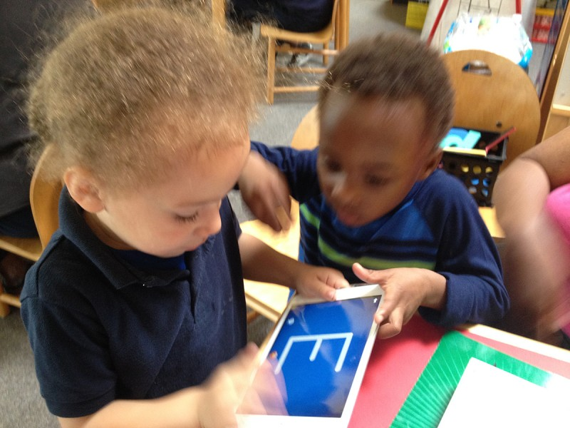 Soraya Harley's four-year-old grandson, Anthony (foreground), traces letters on an iPad during a Tech Goes Home early childhood course in Boston.