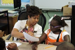Dr. Princess Parker, educational consultant, works with a third grade student at East Sunflower summer school.