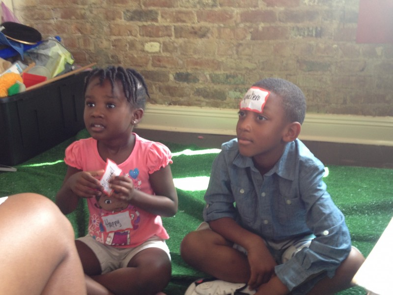 Savannah Watson and Tedrick Glover, both 5, work with three counseling master's students on a self-esteem exercise.