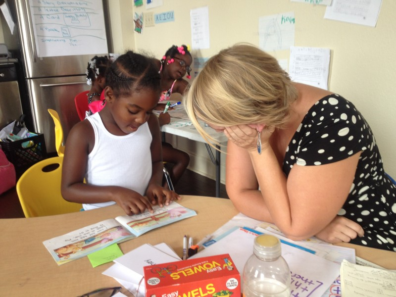 English teacher Elise Butler-Pinkham works with 5-year-old Khaleah.