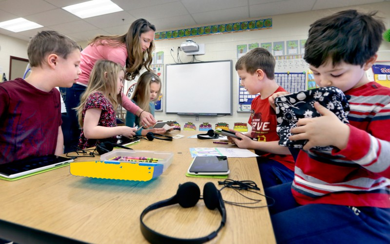 Bass-Hoover Elementary School teacher Jessica DeMarco, standing left, assists some of her students in readying their tablets for a reading assignment in Stephens City, Va., on Tuesday, March 10, 2015.