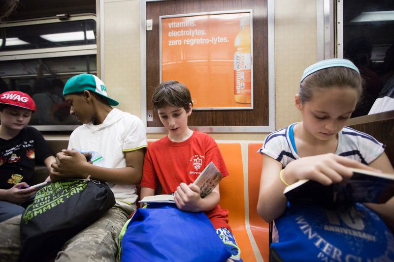 Student Etai Kurtzman, 12, reads a book on the train to Coney Island in Brooklyn, NY May 28, 2015. The group of students from Quest to Learn School took the day trip to Coney Island to analyze user experience on games and rides at Luna Park as part of their late-spring school curriculum.