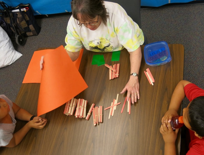 La Vina Witt, a second grade teacher at St. Stephens School, shows students popsicle sticks to represent a three-digit number: two bundles of 100, four bundles of 10 and eight individual sticks make 248. Next she will shield the sticks from view and ask students to add or subtract sticks without being able to recount the whole set.
